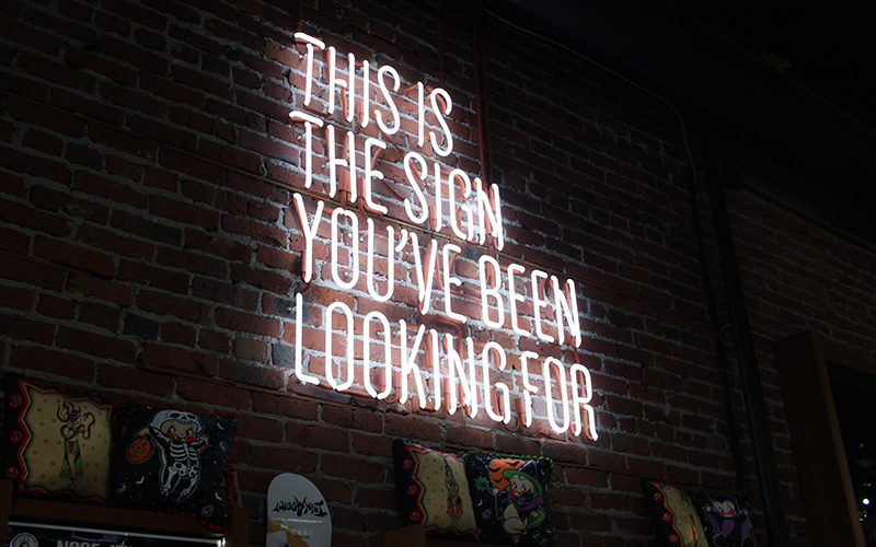 "A large Neon sign on a brick wall with the words ""This is the sign you've been looking for"""
