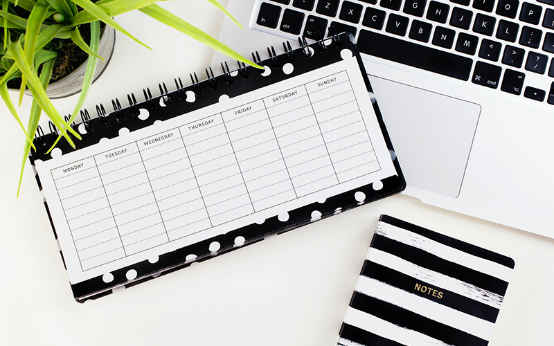 A blank weekly schedule on a desk with laptop