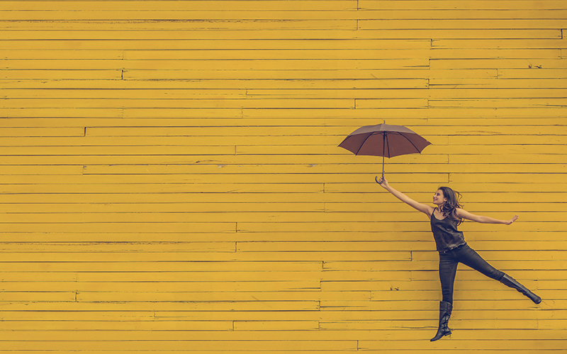 Young lady holding on to an umbrella with black pants and boots on a yellow background