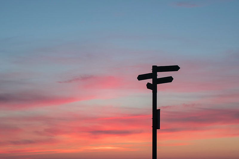 Red and blue sunset with directional signs on a post