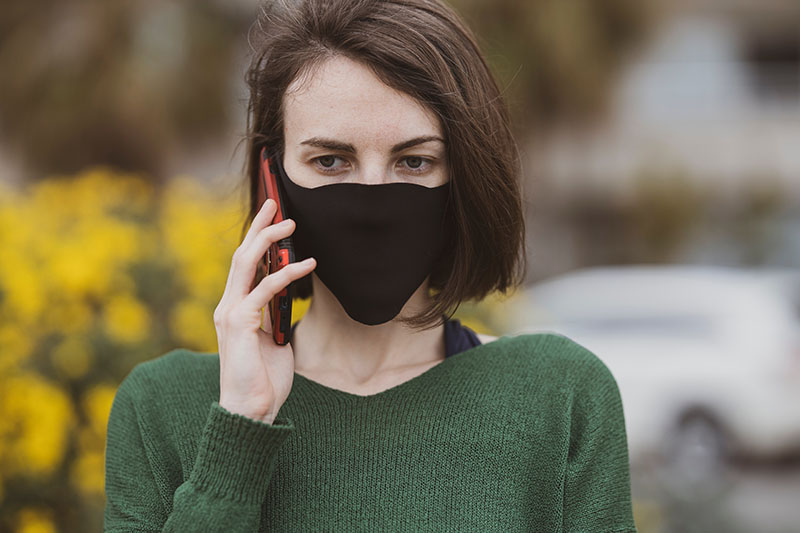 Lady with greeen jersey using her mobile phone, wearing a face mask